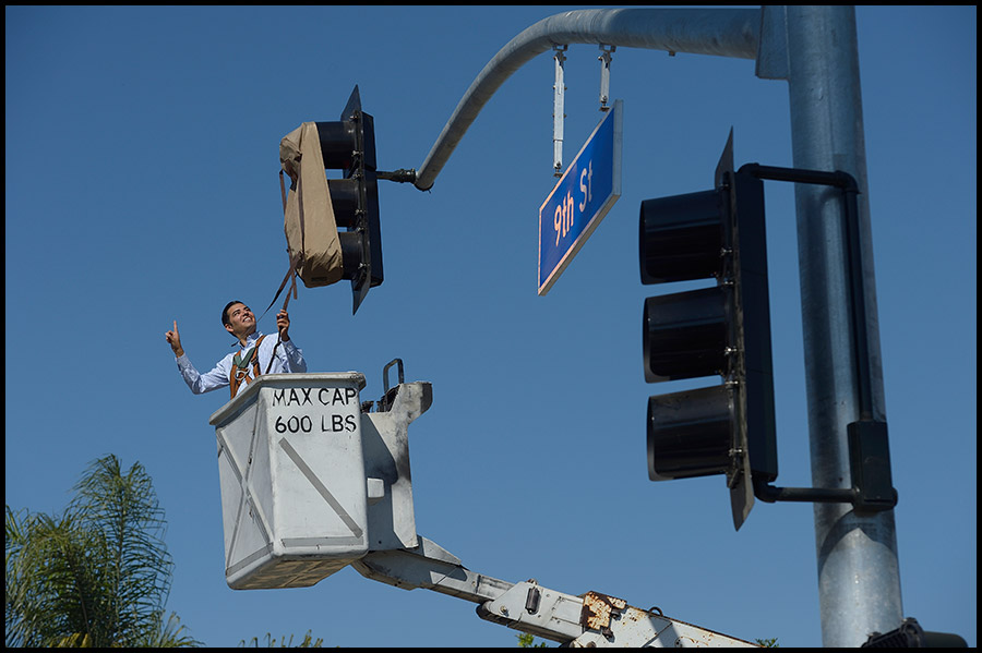 "Long Beach Vice Mayor Robert Garcia prepares to unveil a new traffic signal during a ceremony to turn on the light at the intersection of Pacific Avenue & 9th Street. ""This new traffic signal will make it safer and easier for our residents to cross Pacific Avenue and access the new dog park, schools, businesses, and transit services,"" said Vice Mayor Robert Garcia, who represents the First Council District. The new traffic signal includes enhanced street lighting, pedestrian countdown indications, and a southbound to eastbound left-turn arrow to facilitate left-turns by transit vehicles. The project was funded by the Gas Tax with total project costs estimated at $175,000."