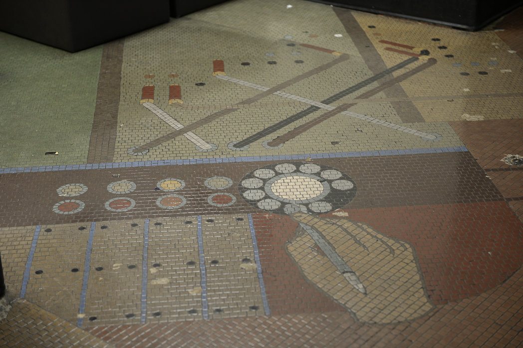 "This mystery photo is a portion of a depression-era floor mosaic by Works Progress Administration artist Grace Clements at the Long Beach Airport. The mosaic was discovered in 2012 when workers lifted decades-old carpet from the first floor of the historic terminal. The portion of the mural pictured shows a hand dialing a telephone with a switchboard above. Other parts of the 72-year old artwork include an oil well, a ship, a large map and a city seal. The elements were supposed to convey Long Beach's origins in aviation, oil and communications. According to the airport's web site, the floor was designed to ""enrich the experience of the traveler, and evoke a larger context for air travel with allusions to other forms of transportation and communication in the world.""  ."