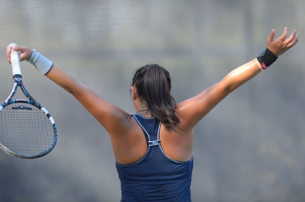 Calvary Chapel's Lauren Saito raises her arms after a point against Laguna Beach's Ashley Fair during their match against at the Costa Mesa Tennis Center on Thursday.