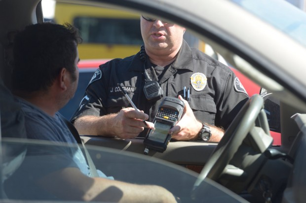 La Habra police officer Jason Coleman issues a ticket using a e-citation machine. The machine connects to a wireless printer in the officer's car to print the ticket. La Habra Police Department is transitioning from paper tickets to electronic citations.