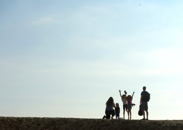 Erica Grover, left, takes a picture of her family, Ella Grover, 10, Mailee Grover, 8, Jonas Grover, 4, and her husband, Bret Grover atop a sand berm in Seal Beach on Friday.
