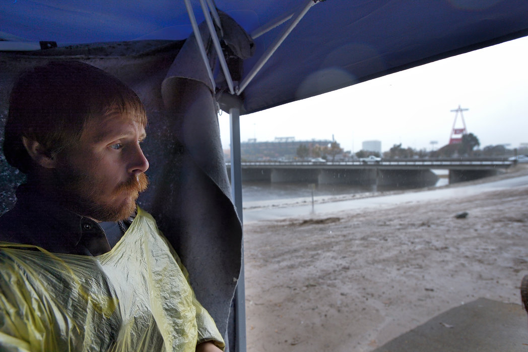 In the shadows of the Big A, Michael Diehl keeps an eye on the rain from inside a tent along the banks of the Santa Ana River in Orange on Tuesday. Diehl said he's been homeless for six months - after exhausting savings on medical bills related to being shot in the head in 2009.